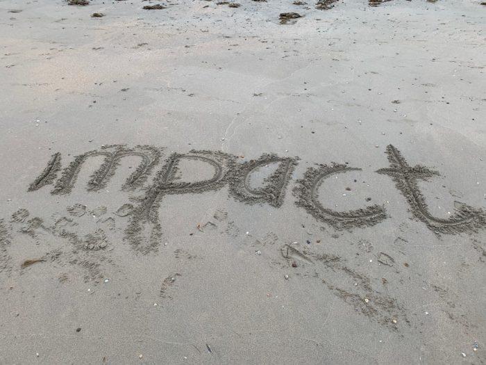 in het zand staat het woord impact geschreven
